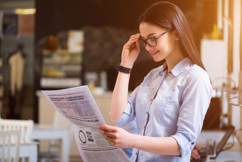 Young Woman with Glasses Reading Newspaper