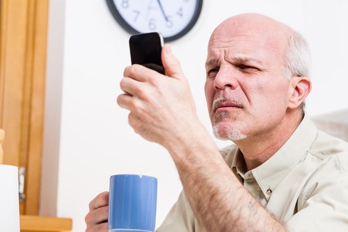 Man Struggling to Read Phone Screen due to Cataracts