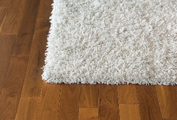 Hardwood floor with a carpet rug on top.