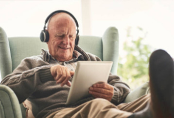 Senior citizen using Bluetooth earphones with tablet computer.