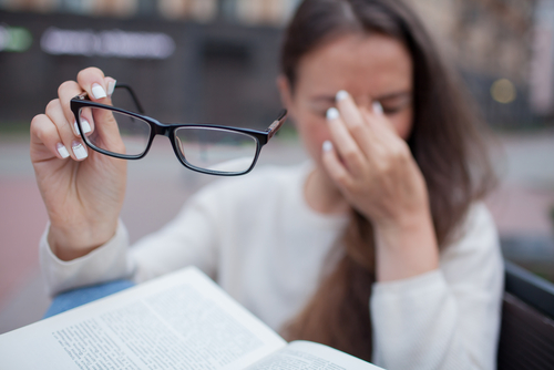 Woman Removing Glasses and Rubbing her Dry Eyes