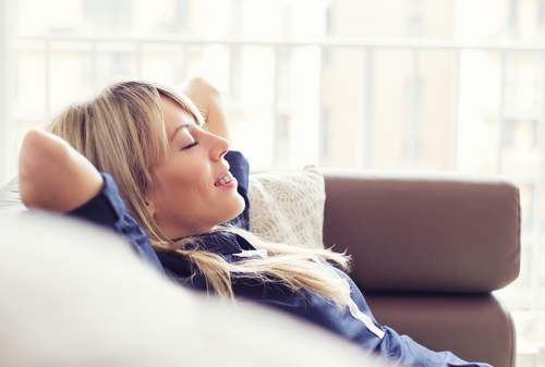 Woman reclining happily on couch
