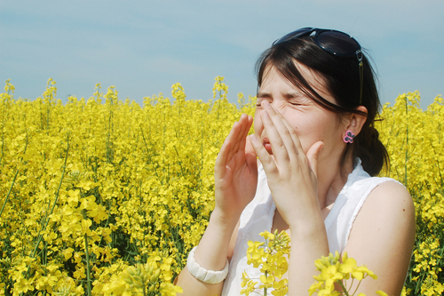 Woman suffering from allergies in field of flowers